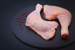 健康食物概念有机未加工的鸡腿新鲜从地方农场和红色干胡椒在黑板岩石头板材 免版税库存图片