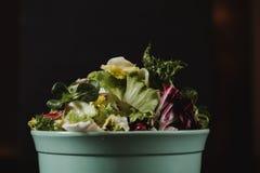 健康食物生活方式概念 在板材的新鲜蔬菜沙拉在土气颜色样式的黑背景 图库摄影