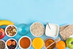 健康食物纤维来源早餐燕麦粥蜂蜜果子苹果香蕉橙汁水绿茶坚果 浅兰的桌面 免版税库存照片