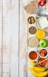 健康食物纤维来源早餐燕麦粥蜂蜜果子苹果香蕉橙汁水绿茶坚果 白色板条木头表 免版税库存图片