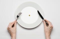 健康食物题材:拿着刀子和叉子在一块板材的手用绿豆在一个白色台式视图 库存照片