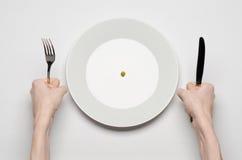 健康食物题材:拿着刀子和叉子在一块板材的手用绿豆在一个白色台式视图 免版税库存图片