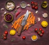 健康食物,烹调和素食概念切板有一棵刀子和切的红萝卜的在谎言成份附近在木rusti 库存照片