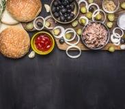 健康食物,烹调和素食概念金枪鱼汉堡与腌汁和橄榄切板在木土气背景t 库存照片