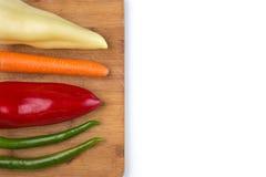 健康食物:在厨房木板和白色背景的未加工的蔬菜 免版税库存照片