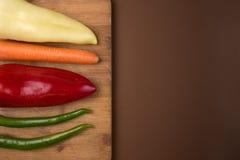 健康食物:在木厨房板的未加工的蔬菜 免版税库存图片