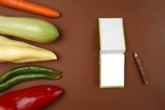 健康食物:在棕色背景和空的笔记本页的未加工的蔬菜您的消息的 免版税库存图片
