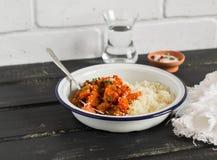健康食物-南瓜炖煮的食物和蒸丸子在白色搪瓷在一个黑暗的木板滚保龄球 素食午餐 免版税库存图片