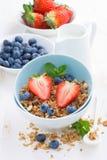 健康食物-格兰诺拉麦片、新鲜的莓果和牛奶,垂直 库存图片