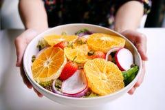 健康饭食, A女性使用手对拿着和递凉拌生菜盘与被保存的三文鱼的, 免版税图库摄影