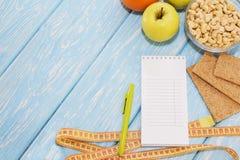健康饮食、健身和减重概念,苹果,笔记薄,铅笔,在桌上的测量的磁带 在视图之上 免版税库存图片