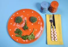 健康饮食与愉快的菜面孔的健康食品概念在板材 库存图片