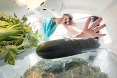 健康饮食:在充分一个开放冰箱的一只手绿色 图库摄影