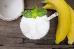 健康香蕉混杂的椰子圆滑的人白色果汁奶昔混合的饮料 免版税库存照片