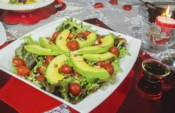 健康鲕梨盘,西红柿,杏仁莴苣和浪漫晚餐的 库存照片