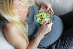 健康,年轻,孕妇坐吃绿色莴苣沙拉的长沙发 免版税库存图片