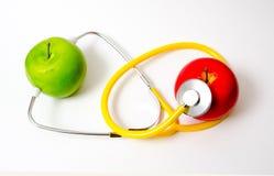 健康:听诊器用被隔绝的苹果 库存图片