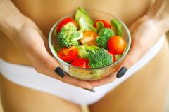 健康 举行在手新鲜的沙拉的亭亭玉立的女孩 白色内衣的女孩 吃健康 饮食 高分辨率 库存照片