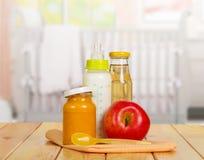 健康婴儿食品:牛奶,汁液,纯汁浓汤,在背景厨房的苹果 免版税库存照片