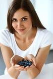 健康维生素食物 美丽的微笑的妇女用蓝莓 免版税库存照片
