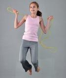 健康年轻肌肉十几岁的女孩跨越横线在演播室 行使与跳跃的孩子高在灰色背景 库存图片