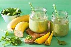 健康绿色圆滑的人用菠菜在玻璃瓶子的芒果香蕉 免版税库存照片