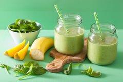 健康绿色圆滑的人用菠菜在玻璃瓶子的芒果香蕉 免版税库存图片