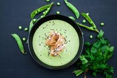 健康绿色汤用火腿和豌豆在背景 免版税库存照片