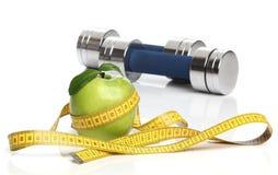 健康绿色苹果和一卷测量的磁带 免版税库存图片