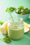 健康绿色菠菜圆滑的人用在玻璃瓶子的芒果香蕉 免版税库存照片