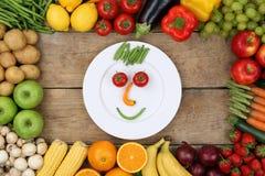 健康从菜的吃微笑的面孔在板材 免版税图库摄影
