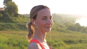 健康活跃生活方式 听到音乐的年轻可爱的慢跑者妇女 股票录像