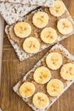 健康素食主义者自创大块的花生酱和香蕉三明治用瑞典整个五谷薄脆饼干在木切板 免版税库存图片