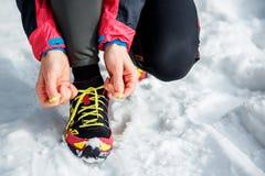健身、体育、人们和生活方式概念-接近栓鞋带的一名年轻运动的妇女户外在冬天 免版税库存图片