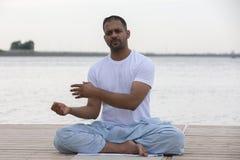 健身、体育、瑜伽和健康生活方式概念-关闭思考在容易的坐的姿势的人在河或湖停泊处 库存照片