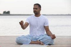 健身、体育、瑜伽和健康生活方式概念-关闭思考在容易的坐的姿势的人在河或湖停泊处 免版税库存图片