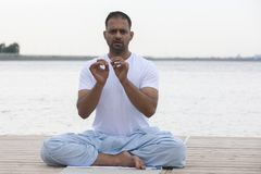 健身、体育、瑜伽和健康生活方式概念-关闭思考在容易的坐的姿势的人在河或湖停泊处 图库摄影