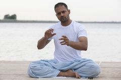 健身、体育、瑜伽和健康生活方式概念-关闭思考在容易的坐的姿势的人在河或湖停泊处 免版税图库摄影