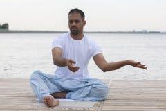 健身、体育、瑜伽和健康生活方式概念-关闭思考在容易的坐的姿势的人在河或湖停泊处 免版税库存照片