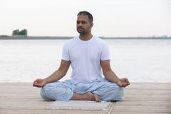 健身、体育、瑜伽和健康生活方式概念-关闭思考在容易的坐的姿势的人在河或湖停泊处 库存图片