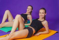 健身、体育、训练和生活方式概念-微笑做在席子的两名运动的妇女锻炼在健身房 图库摄影