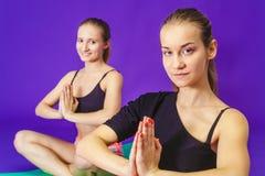 健身、体育、训练和生活方式概念-微笑做在席子的两名运动的妇女锻炼在健身房 免版税图库摄影