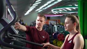 健身、体育和活跃生活方式-教练员和年轻女人健身房的 股票录像