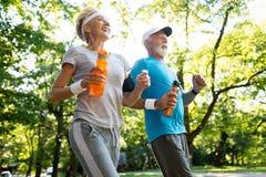 健身、体育,人,行使和生活方式概念-资深夫妇赛跑 库存照片