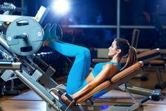 健身、体育,体型,行使和人概念-屈曲在腿新闻机器的少妇肌肉在健身房 免版税库存图片