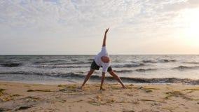 健身人实践的瑜伽asana,当在海海滩时的早晨训练 股票录像