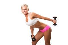 健身体育妇女微笑满意对哑铃 免版税图库摄影