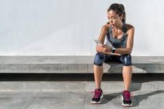 健身使用音乐手机app的赛跑者女孩 免版税库存照片
