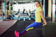 健身俱乐部的女孩 做蹲坐的年轻女运动员使用在健身房的长凳 库存照片