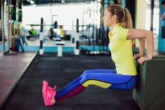 健身俱乐部的女孩 做蹲坐的年轻女运动员使用在健身房的长凳 免版税库存图片